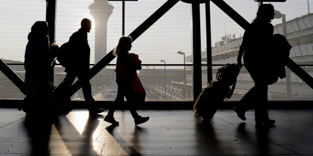 Travelers walk through terminal 3 at O'Hare International airport in Chicago, Sunday, Dec. 1, 2013. It's a holiday tradition