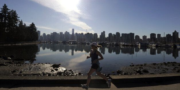 A woman joggs in Stanley Park in front of the Vancouver Skyline on February 19, 2010, during the Vancouver Winter Olympics.