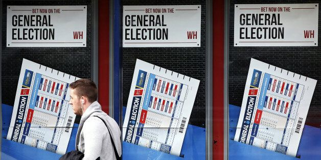 A member of the public walks past a betting shop window with a display for the General Election in Govan, Scotland, Wednesday