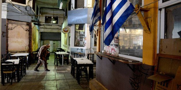 A man walks past a Greek flag in the central market of the northern port city of Thessaloniki , Greece, Wednesday, April 29,