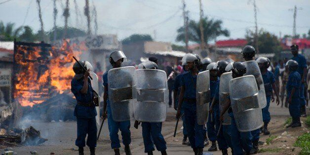Police march past burning barricades down the main road in the Cibitoke neighbourhood of Bujumbura, on May 7, 2015. At least