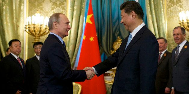 Russian President Vladimir Putin, left, shakes hands with his Chinese counterpart Xi Jinping during their meeting in Moscow's