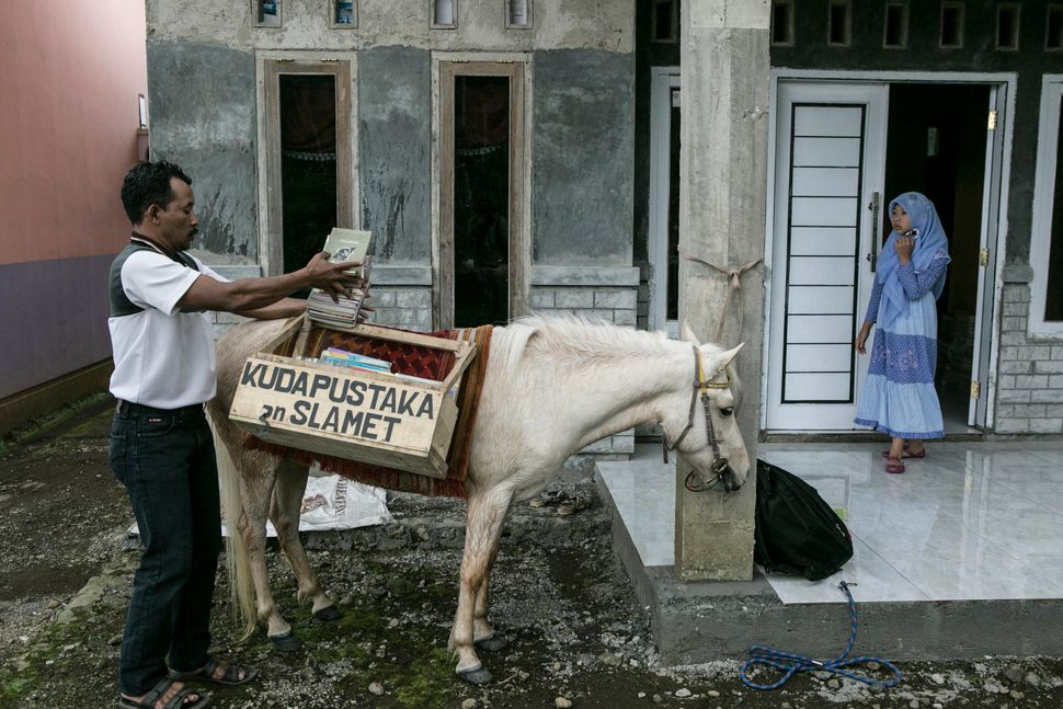 Ridwan Sururi loads books onto his horse in Serang Village, Indonesia, May 5, 2015.