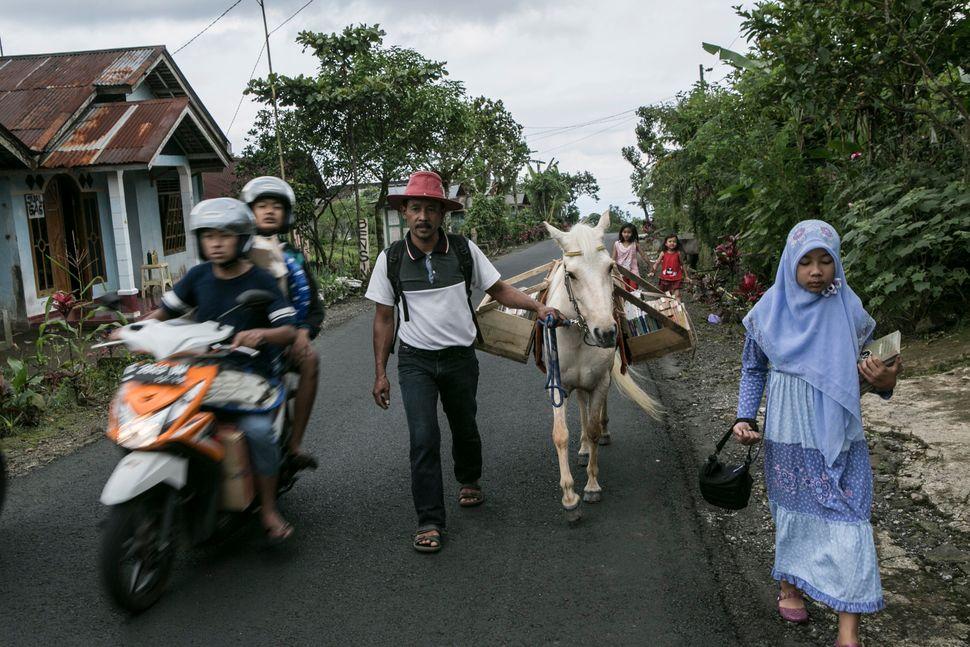 Sururi, his daughter Indriani Fatmawati and his horse Luna walk to Miftahul Huda Islamic elementary school in Serang Village