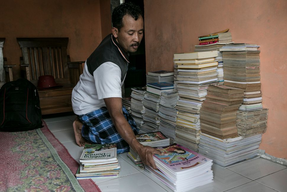 Sururi prepares books for the mobile library at his house in Serang Village on May 5, 2015.