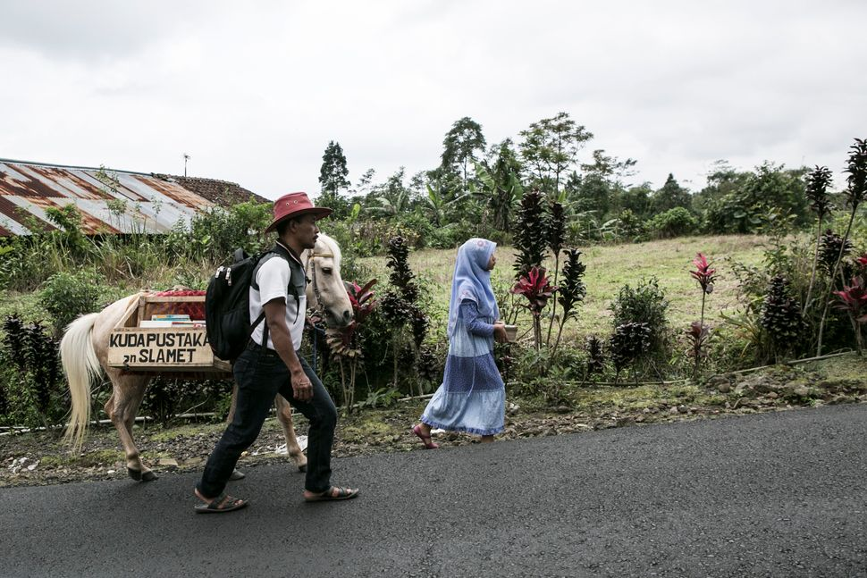 Sururi and his daughter walk to school on May 5, 2015.