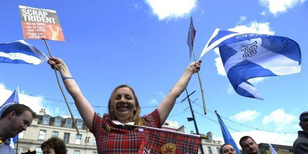 A demonstrator wearing a tartan dress waves Saltire flags, the national flag of Scotland, during a pro-independence rally in