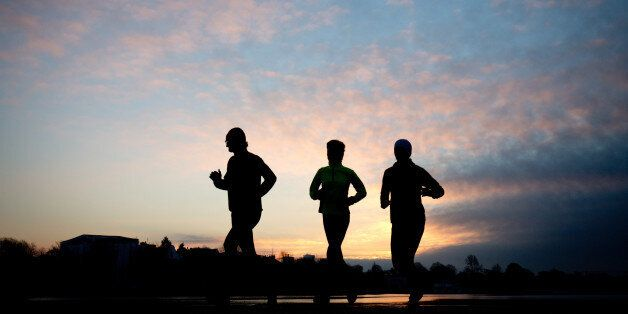 Three runners are silhouetted as they run past the Aussenalster lake in Hamburg, northern Germany, Wednesday morning, Feb. 4,