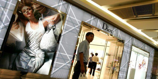 A man walks past a Dior store in Beijing Saturday Aug. 25, 2007. After generations of poverty many Chinese can now afford to