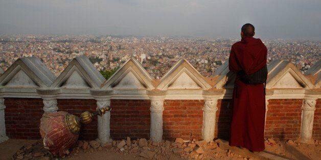 A Buddhist monk catches an aerial view of Kathmandu from the damaged Swayambhunath Stupa premises in Kathmandu, Nepal, Wednes