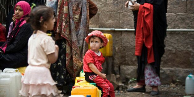 A girl waits for her turn to fill buckets with water from a public tap amid an acute shortage of water, in Sanaa, Yemen, Satu