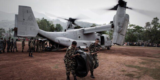 Nepalese soldiers unload relief supplies from an US Osprey aircraft at Dhading Besi, some 100 kms north west of Kathmandu on