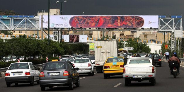 In this photo taken on Sunday, May 10, 2015, cars drive under a billboard showing a copy of an old painting which decorates a