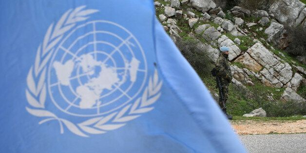 A United Nations flag waves as Spanish U.N. peacekeepers carry out a foot patrol in the disputed Chebaa Farms area between Le