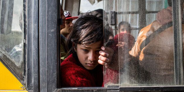 KATHMANDU, NEPAL - APRIL 29: A young girl waits on board a bus to be evacuated from the city center on April 29, 2015 in Kath