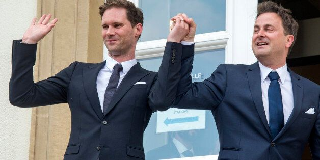 Luxembourg's Prime Minister Xavier Bettel, right, holds up the hand of his partner Gauthier Destenay, with a wedding band on