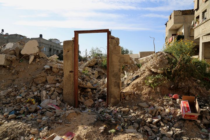 An empty frame doorway is seen standing on the rubble of a destroyed building that was damaged in last summer's Israel-Hamas