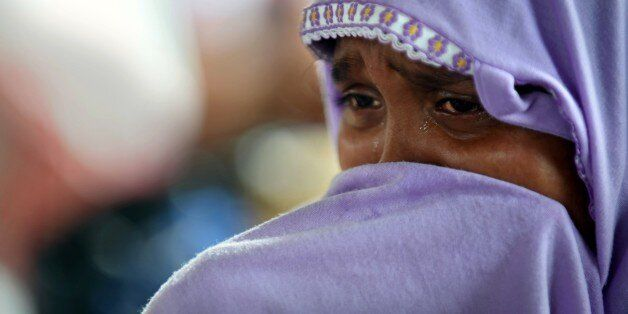 Hasina Begam, a rescued migrant Rohingya woman, cries as she grieves for her brother from the new confinement area in the fis