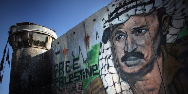 RAMALLAH, WEST BANK - AUGUST 24:  A mural of the late Palestinian leader Yasser Arafat adorns the wall of the Israeli seperat