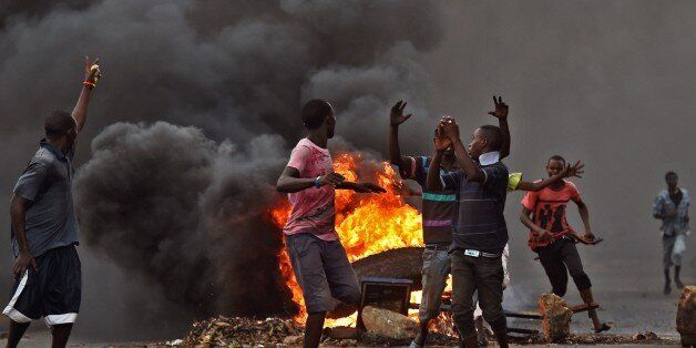 Protestors opposed to the Burundian president Pierre Nkurunziza's  third term in office gather by a burning barricade during
