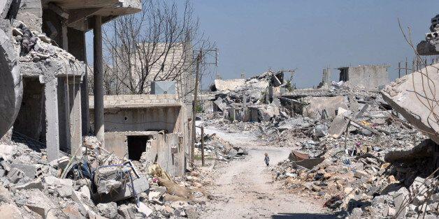 In this picture taken on Saturday, April 18, 2015, a Kurdish boy, center background, walks between buildings that were destro