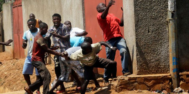 Protester throw stones at police during clashes in the Nyakabyga neighborhood of Bujumbura, Burundi, Thursday May 21, 2015. P