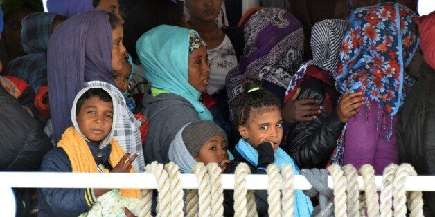 Migrants wait to disembark from Migrant Offshore Aid Station (MOAS) ship in the port of Messina, on May 16, 2015 following re