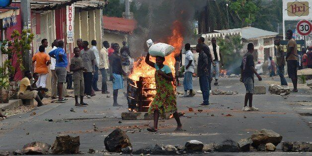 A woman walks past a burning barricade, erected by protestors opposed to the Burundian President's third term, in the Kinanir