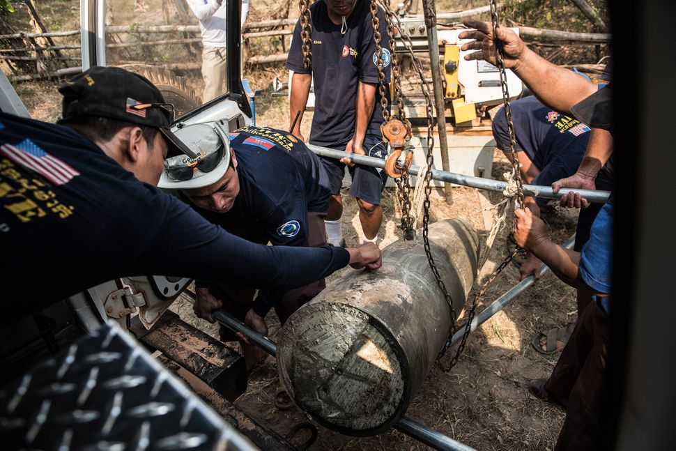 Members of the dive team load the cut sections of a large bomb they retrieved from the Mekong River. The bomb's head and tail