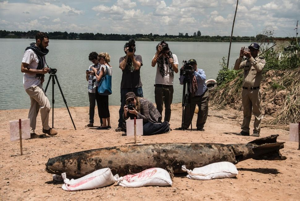 Journalists stand in line to photograph the American MK82 bomb the divers pulled from the river.