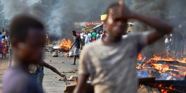 Protestors stands near a burning barricade during a demonstration against Burundian President's third term candidature in the