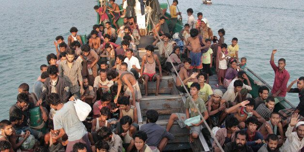 FILE - In this Wednesday, May 20, 2015 file photo, migrants wait to be be rescued by Acehnese fishermen on their boat on the