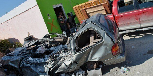 A car lies destroyed in front of a house after a tornado struck May 25, 2015 in Ciudad Acuna, northern Mexico, leaving at lea