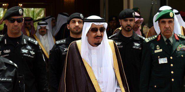 Saudi King Salman bin Abdulaziz (C) walks surrounded by security officers to receive Bahraini King Hamad bin Isa al-Khalifa (