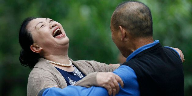 A Chinese woman laughs during a social dance with a man at Ritan Park in Beijing, China Thursday, Oct. 30, 2014. Levels of se
