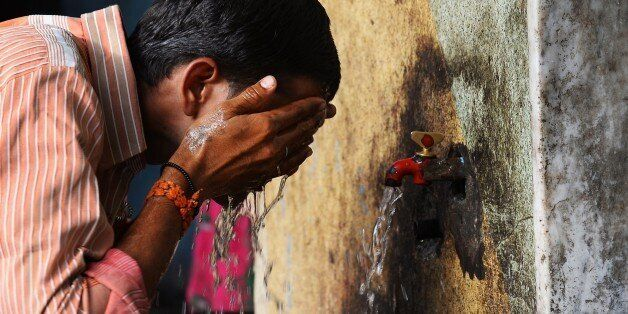 An Indian man washes his face at a roadside tap during rising temperatures  in New Delhi on May 28, 2015. Hospitals in India
