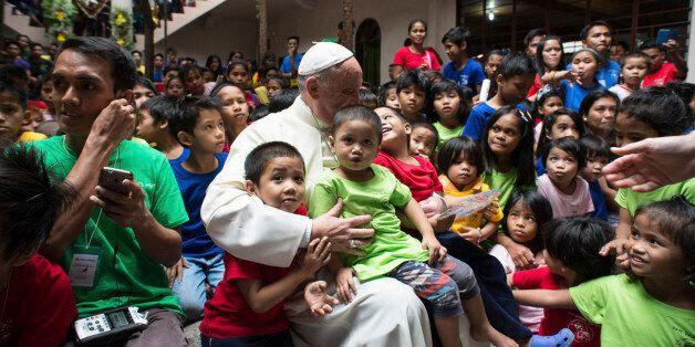 Pope Francis sits with children of the Anak-Tnk Foundation, founded in 1998 by a Jesuit priest, which helps homeless children