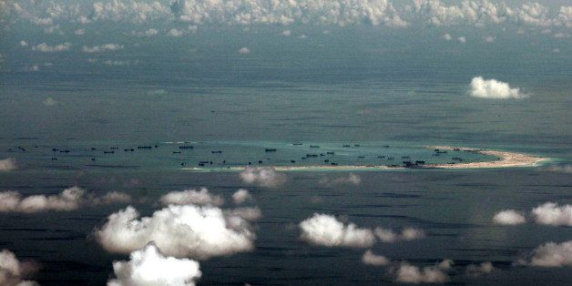 This areal photo taken through a glass window of a military plane shows China's alleged on-going reclamation of Mischief Reef