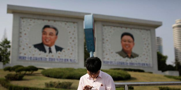 In this Tuesday, May 5, 2015, photo, a man sits in front of portraits of the late North Korean leaders Kim Il Sung, left, and
