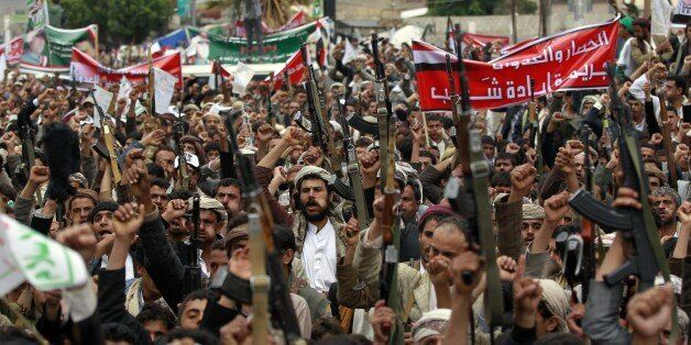 Supporters of the Shiite Huthi movement brandish their weapons during a demonstration against the Saudi-led air strikes, in t