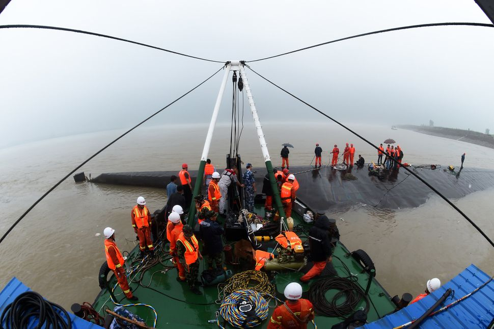 Rescuers save survivors at the site of the overturned passenger ship.