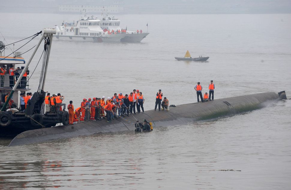 Rescuers pull a person from the water as they search for survivors.