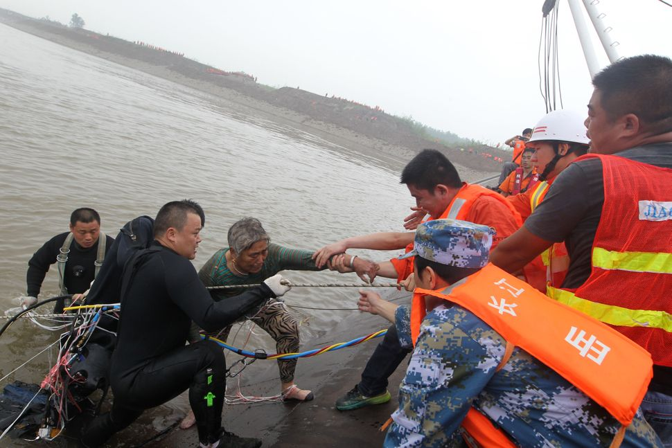 A survivor is saved from the overturned passenger ship.