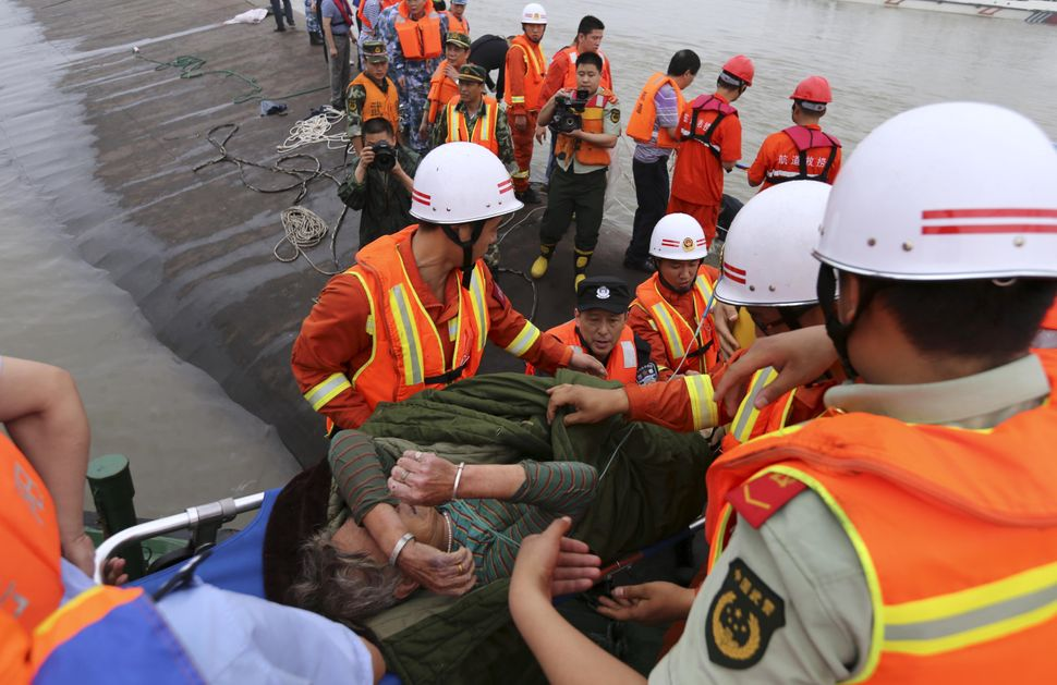 An elderly survivor is carried onto the river bank after being rescued.