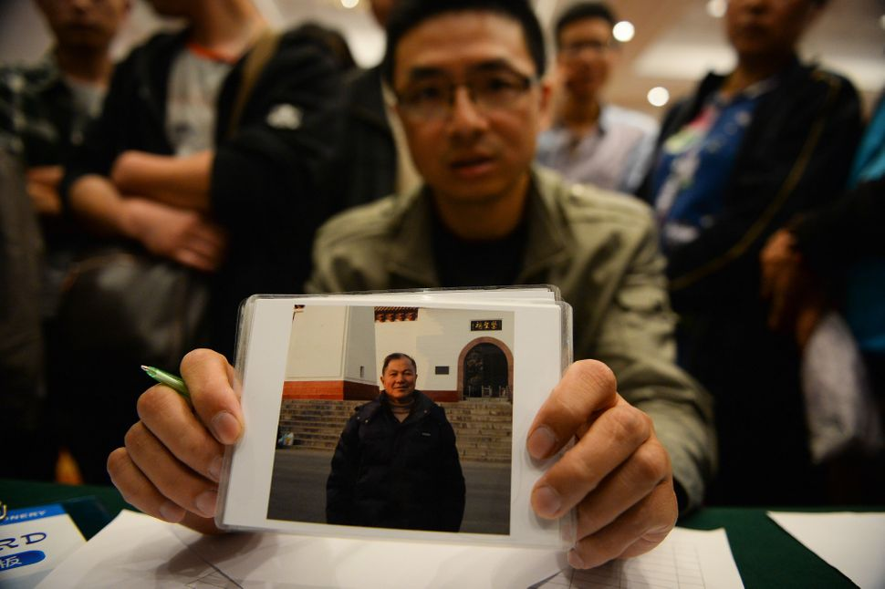 A man shows the photo of his father-in-law, who was traveling on the overturned ship.