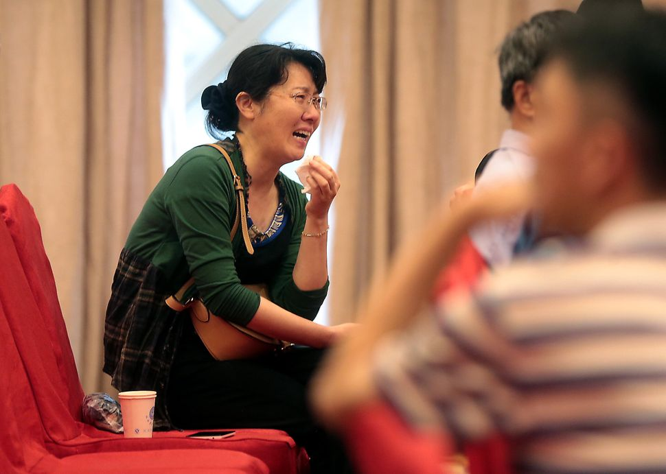 Relatives of passengers wait for news at the Shijiyuan Hotel.
