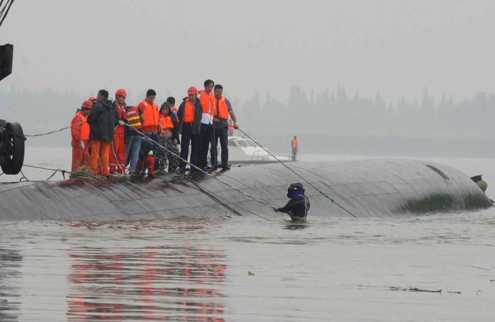 A diver walks into the water as rescue teams search for survivors.