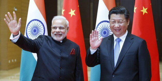 India's Prime Minister Narendra Modi (L) and China's President Xi Jinping wave to journalists before they hold a meeting in X
