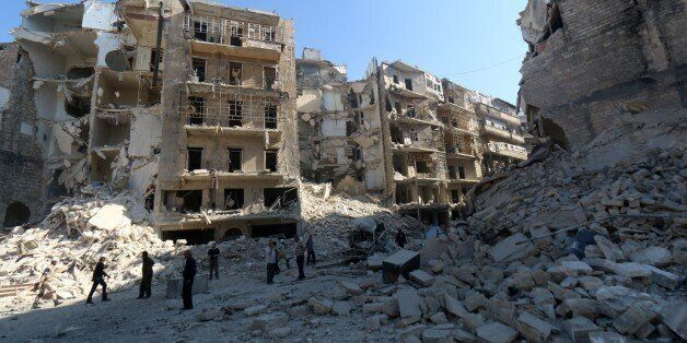 Syrians stand amidst the destruction in the eastern Shaar neighbourhood of the northern Syrian city of Aleppo on May 30, 2015