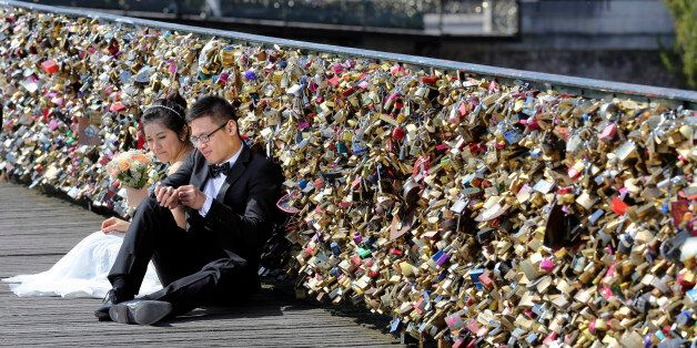 FILE - This Wednesday April 16, 2014 file photo shows a newly wed couple resting on the Pont des Arts in Paris, France. Any h